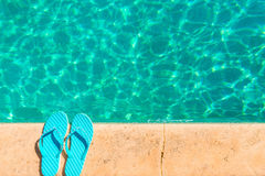 Turquoise flip flops at the edge of  pool Stock Images