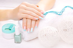 Turquoise french manicure with light towel Royalty Free Stock Image