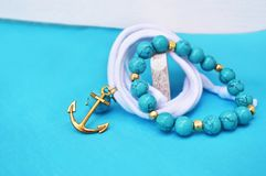 Turquoise gemstone bracelet - nautical jewelry with gold anchor stock images