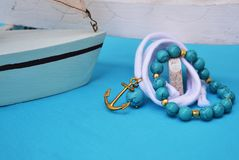 Turquoise gemstone jewelry - nautical jewelry with gold anchor royalty free stock photography