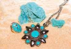 Turquoise gemstones. With a pendant and ring with polished cabochons and a specimen of massive natural stone, used by ancient civilisations as a talisman Royalty Free Stock Photos