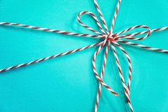 Red and white rope bow on a blue background. Turquoise gift box background stock image