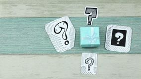 Turquoise gift box under questions. Sketches of question marks on paper and gift boxes stock video footage