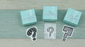 Turquoise gift boxes and questions. Sketches of question marks on paper and gift boxes stock video