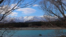 The turquoise glacial lake. Is enchanted. Severe snowy peaks attract the eye and make you think about eternity. Cumulus clouds slowly float across the blue sky royalty free stock photos