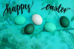 Multicolored easter eggs on turquoise background, black inscription Happy Easter. Turquoise and green easter eggs on a background, black inscription happy Easter Royalty Free Stock Image