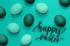 Turquoise and green easter eggs on a background, inscription happy Easter. Turquoise and green easter eggs on a background, black inscription happy Easter Royalty Free Stock Images