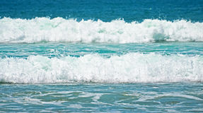 Turquoise green waves with foam on a sandy beach in Indonesia Royalty Free Stock Photography