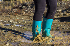Turquoise gumboots splashing in a puddle Stock Image