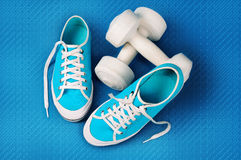 Turquoise gym shoes and white dumbbells on a blue sports mat Royalty Free Stock Photography