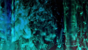 Turquoise ink in water. Black background. HD (1920x1080). Fuzzy dark and light viridan fibres and threads slowly intertwine and swirl stock footage