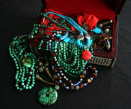 Turquoise Jewels and Gemstones. Ethnic type jewels, gemstones,turquoise,coral,gold,ethnic ornaments, orange silk in a scarlet coloured felt lined mosaic Stock Photography