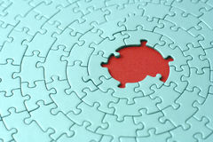 Turquoise jigsaw with missing pieces in the red center stock photos