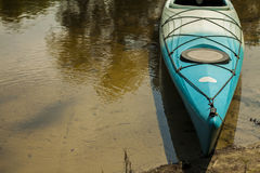 Turquoise kayak by the river. Kayak on the river bank, nobody Stock Image