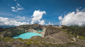 Turquoise Kelimutu crater lake surrounded by rocky hills. Turquoise Kelimutu crater lake surrounded by brown rocky hills under blue sky with white clouds at stock video