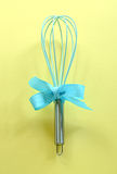 Turquoise kitchen whisk on yellow background Stock Photography