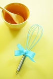 Turquoise kitchen whisk on yellow background Royalty Free Stock Photos