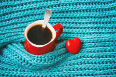 Turquoise knitted woolen scarf, red mug with coffee, heart Royalty Free Stock Photography
