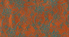 Turquoise lace on orange background. Stock Photo