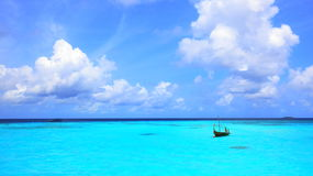 Turquoise lagoon at Maldives. Panorama of the turquoise lagoon at Maldives with a small boat and beautiful clouds Stock Images