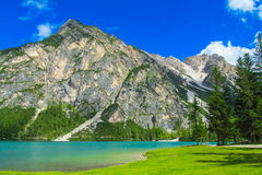 Turquoise lake in the Alps. Beautiful rocky peaks, mountain of gray stones, deep blue lake on sunny day Royalty Free Stock Images