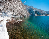 Turquoise lake banks covered with snow. Turquoise lake banks covered with white snow under blue sky. Plitvice national park, popular touristic destination of Stock Photos