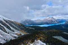Turquoise  lake in Canadian Rockies. Snowfall in mountains  covered with fresh snow and golden larches forest in autumn. Banff National Park. Spray Lake Stock Photo