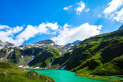Turquoise lake with green hills around and the snowy mountains i Royalty Free Stock Images