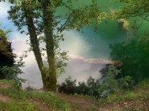 Turquoise lake with sky reflection and trees. Unspoiled nature. Beautiful colours. With submerged wall, ruin detail Stock Photo