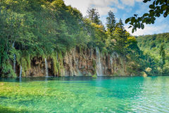 Turquoise lake and waterfalls. Croatia. Clear water at Plitvice lakes national Park, in the background a large waterfall, around the green trees and bushes. Blue Stock Images