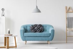 Turquoise living room interior. Knot pillow on turquoise sofa in living room interior with gray lamp, ladder and wooden table Royalty Free Stock Photos