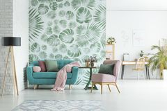 Apartment with floral wallpaper. Turquoise lounge with pink blanket and pillows standing in stylish apartment interior with floral wallpaper Stock Photo