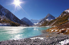 Turquoise mountain lake under the ice with blue sky and sun Royalty Free Stock Image