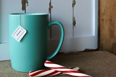 Cup of tea with a dream tag. Turquoise mug of hot  tea with a dream tag and peppermint sticks against a rustic background of wood and burlap Stock Image