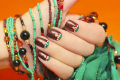 Turquoise nails. Women's nails are covered with brown varnish with the design of white,red and turquoise points on an orange background with a bracelet made of stock photography
