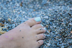 Turquoise nails of a women on the sand beach Stock Images