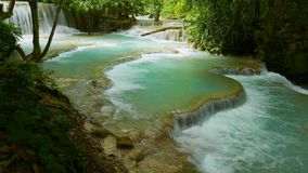 Rain forest landscape with cascading water stream. Turquoise natural swimming pools of the Kuang Si Falls, one of southeast Asia's most beautiful water falls stock video footage