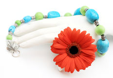 Turquoise necklace over hand with red orange daisy. Green and blue turquoise nugget necklace over White display hand holding red orange daiisy Royalty Free Stock Photography