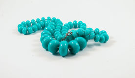 Turquoise necklace of plastic on a white background stock photography