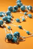 Turquoise necklaces over orange background Royalty Free Stock Photo