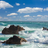 Turquoise ocean waves,  rocks coastline and  blue sky Stock Image