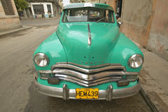 Turquoise old Dodge parked in front of old buildings in Havana, Cuba Royalty Free Stock Images
