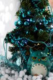 Turquoise owl sitting under a Christmas tree in a decorated bowls, garlands, tinsel, artificial snow royalty free stock photography