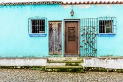 Turquoise painted house exterior with decorated wrought iron bar royalty free stock images