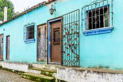 Turquoise painted house exterior with decorated wrought iron bar stock photography