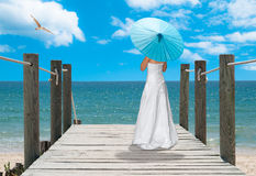 The Turquoise Parasol. Girl with turquoise blue parasol looking out across the ocean royalty free stock images
