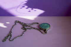 Turquoise pendant. Silver chain with nice turquoise pendant on purple background with shadows Royalty Free Stock Images
