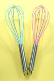 Turquoise and pink kitchen whisks on yellow background Royalty Free Stock Photography