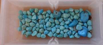 Turquoise in a plastic container. Royalty Free Stock Image
