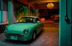 Turquoise retro car in the night garage in the light of the light. The calm after a day`s work Royalty Free Stock Photos